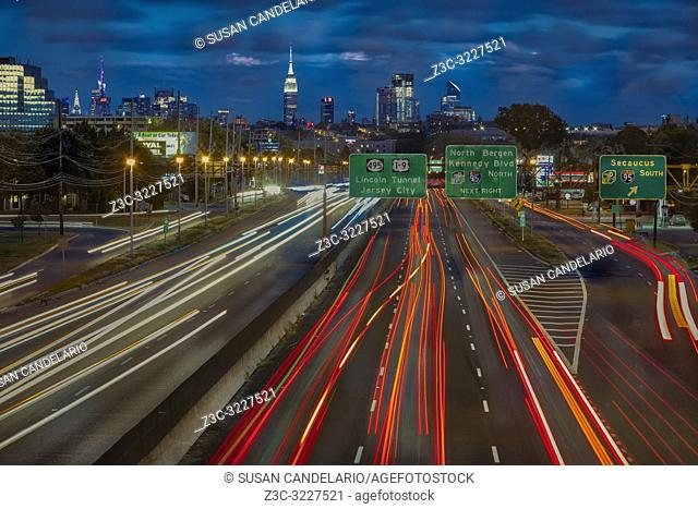 Path To And From NYC - Vehicular light trails from route 3 in New Jersey lead to a view of the New York City skyline.