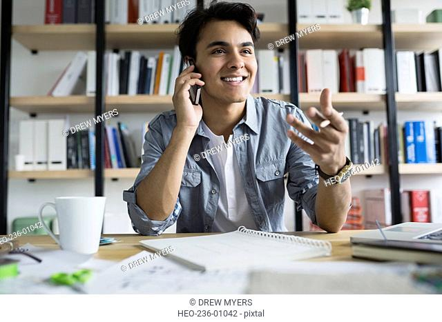 Architect talking on cell phone in office