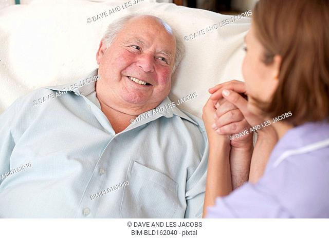 Caucasian nurse talking to patient in bed