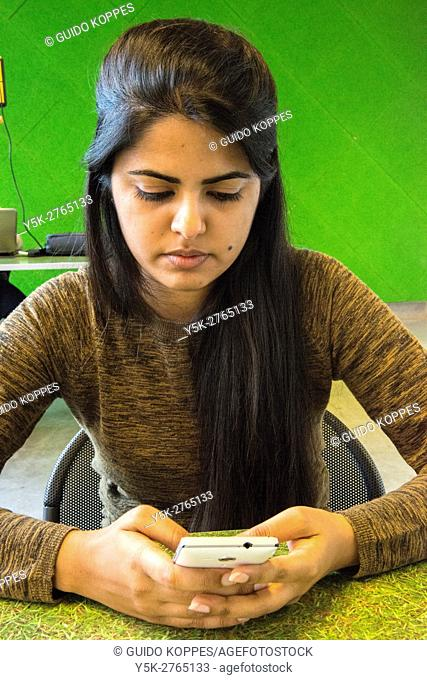 Aachen, Germany. Indian echange student to Aachen University using her smartphone while sitting at a student's study desk
