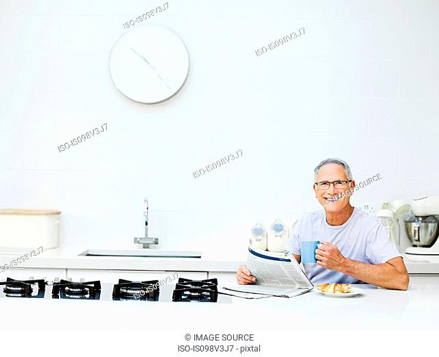 Senior man having breakfast, reading newspaper