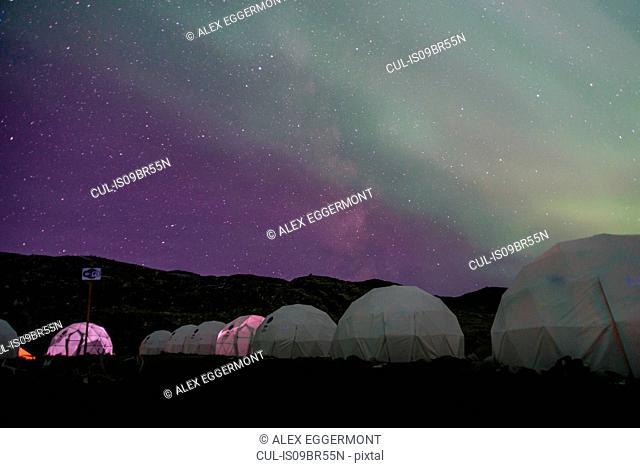 Aurora borealis over row of dome tents, Narsaq, Vestgronland, Greenland