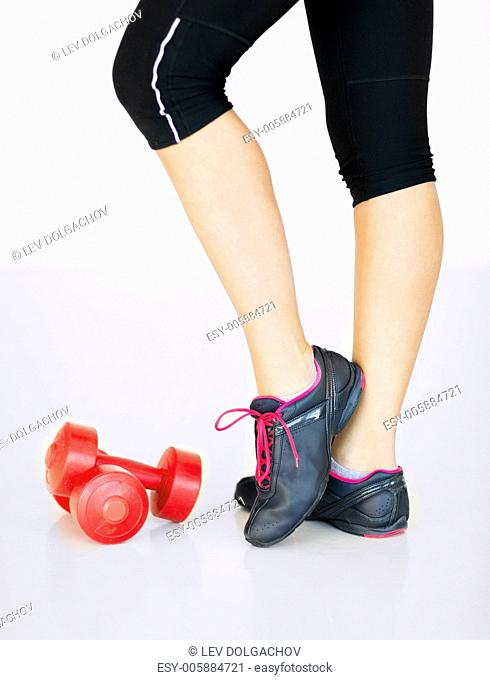 sport and recreation concept - sporty woman legs with light red dumbbells