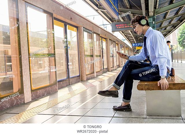Businessman waiting for train sitting on bench