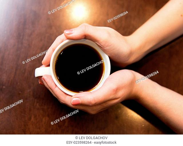 drinks, people and lifestyle concept - close up of woman hands holding cup with hot black coffee
