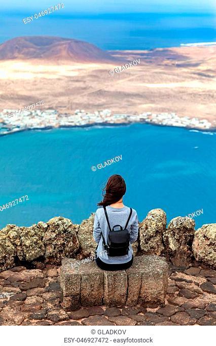 Traveler woman enjoying beautiful seascape at viewpoint on island. Travel concept. La Graciosa Island, Mirador del Rio, Lanzarote, Canary Islands