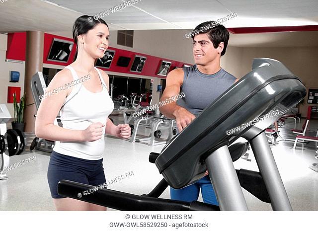 Man assisting a woman on a treadmill