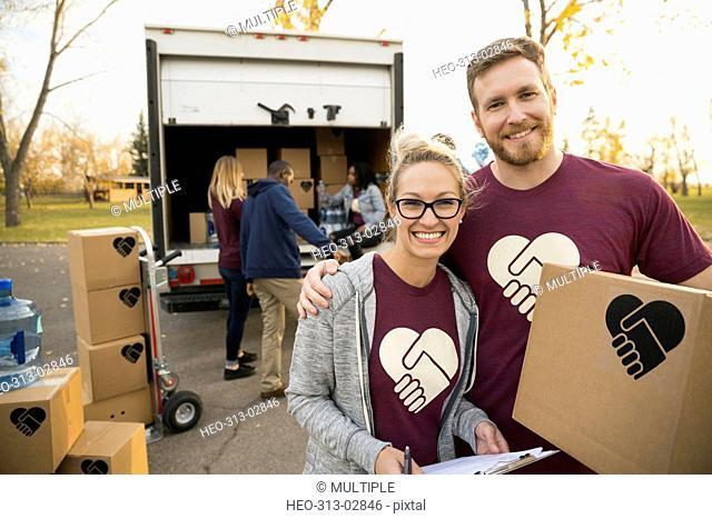 Portrait smiling volunteers unloading cardboard boxes from truck