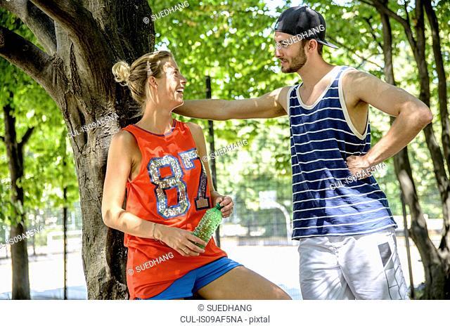 Basketball couple taking a break in city park