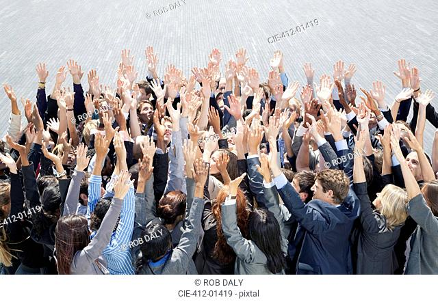 Crowd of business people cheering with arms raised