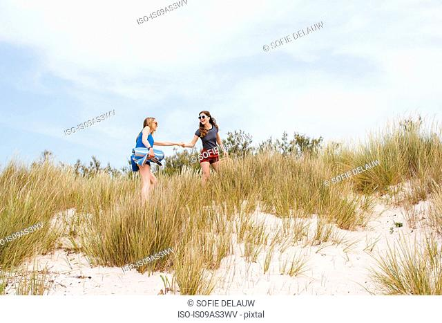 Two young female friends running and holding hands on sand dunes