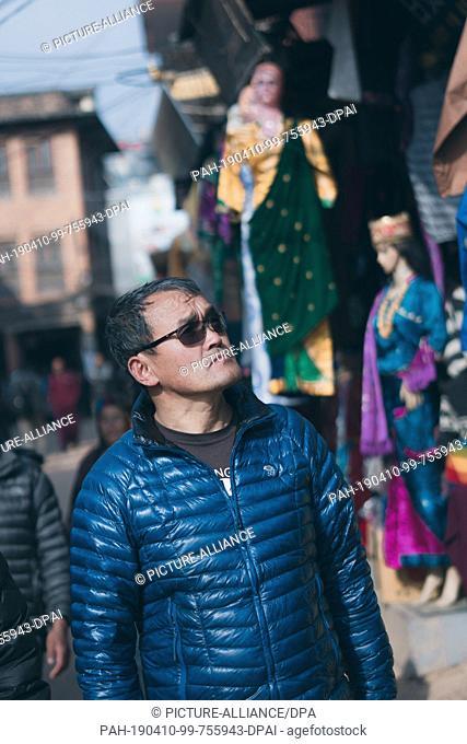 30 January 2019, Nepal, Kathmandu: Lhakpa Gelu Sherpa, 52 year old mountain guide from Nepal, passes the Buddhist monastery on a path