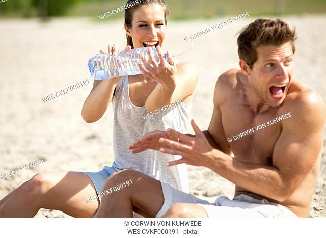 Playful couple splashing with bottle of water on the beach