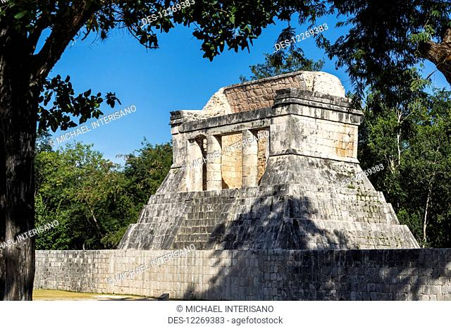 Ancient Mayan Temple with round columns framed by trees and blue sky; Chichen Itza, Yucatan, Mexico