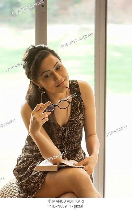 India, Woman holding big glasses and book sitting on stool