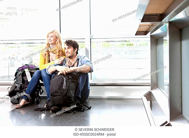 Couple sitting on floor in airport
