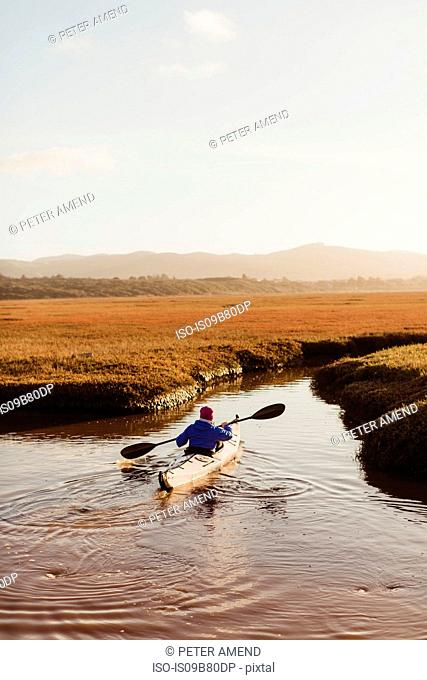 Rear view of woman kayaking on river, Morro Bay, California, USA