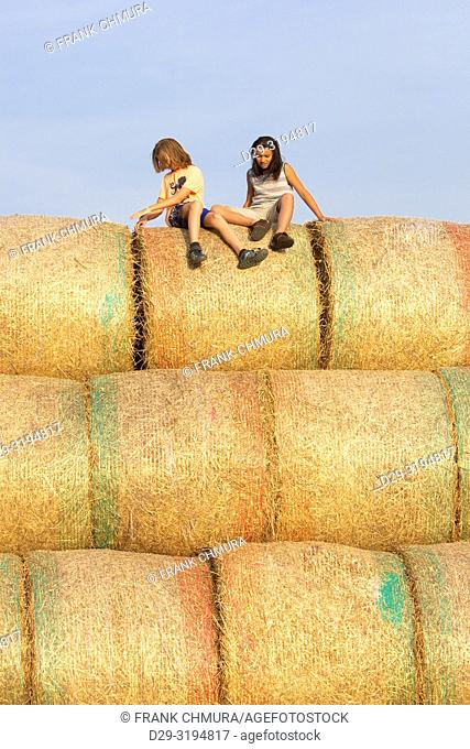 Czech Republic, Southern Bohemia - Two Boys Having Fun with Bales of Hay in Summer