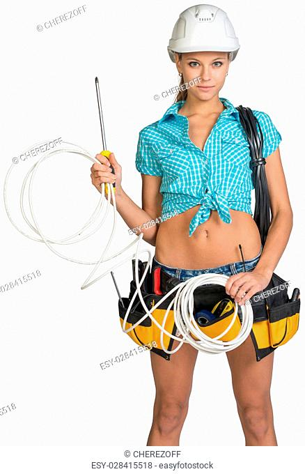 Woman wearing hard hat and tool belt, with coil of power cable on her shoulder, holding coil of cat 5 and screwdriver, looking at camera