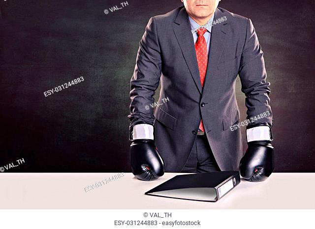 portrait of a male office worker with boxing gloves in the defensive stance