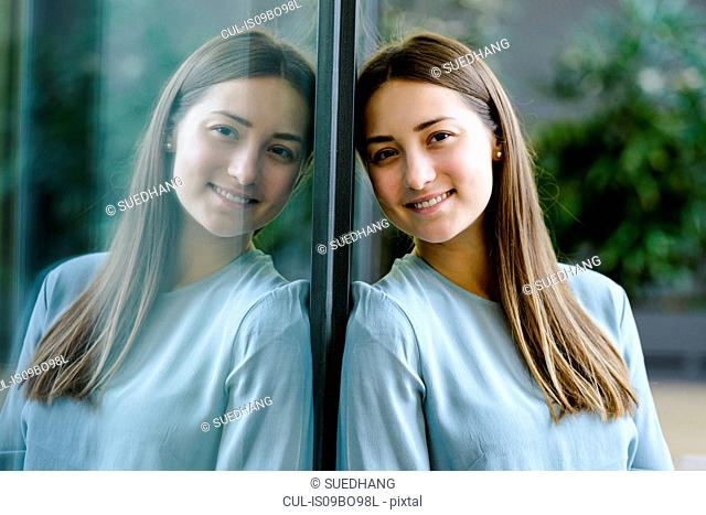 Woman and her mirror reflection on glass wall