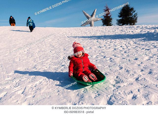 Girl in red knit hat tobogganing down snow covered hill