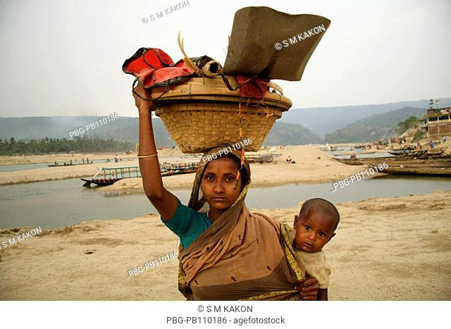 Woman stone worker returns home with her child Jaflong, Sylhet, Bangladesh March 2008