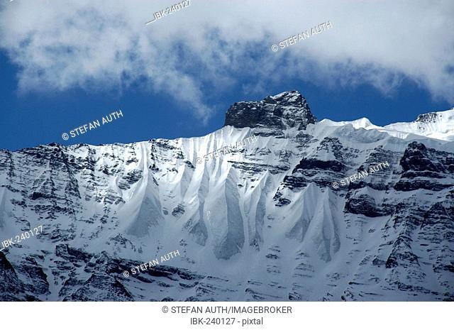 White cloud and blue sky above ice-capped summit near Khangsar Annapurna Region Nepal