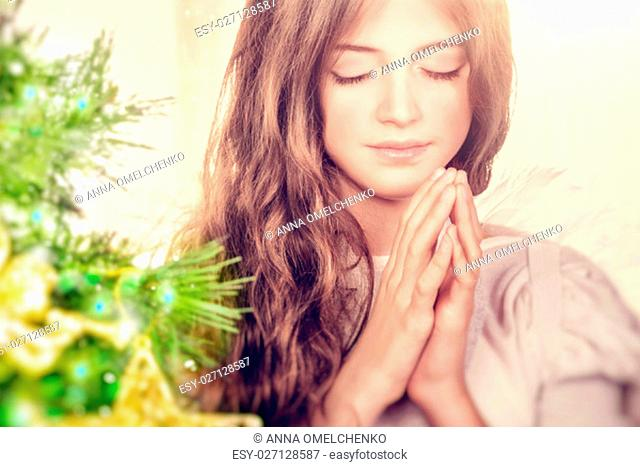 Closeup portrait of a beautiful calm girl with closed eyes praying near Christmas tree, gentle young angel wishing peace and harmony for everyone