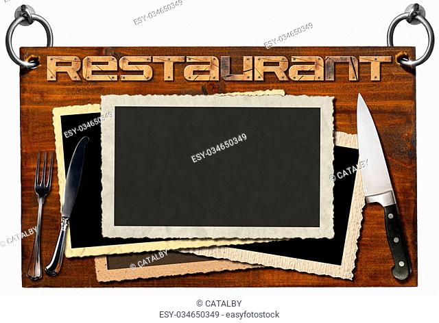 Advertising dark wooden sign with clipping path for a restaurant with blank aged photo frames, kitchen knife and silver cutlery