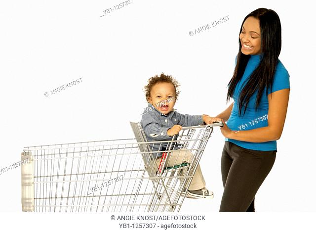 Attractive young mother with one year old son in shopping cart or trolley