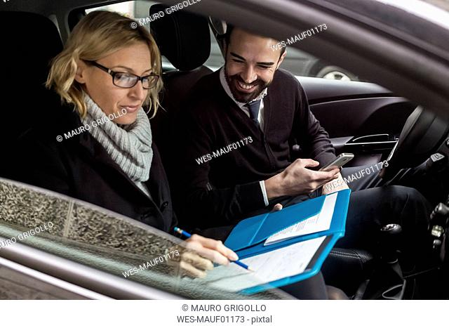 Businessman and businesswoman with documents in car