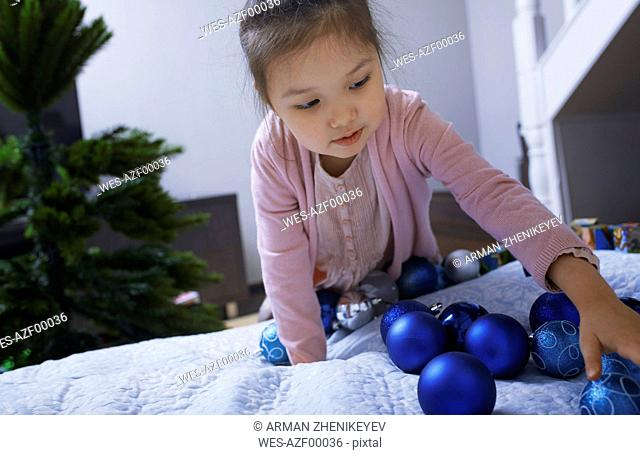 Portrait of little girl with blue Christmas baubles at home