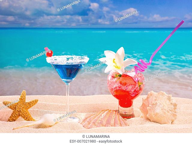 Beach tropical red and blue cocktail on caribbean white sand flower and seashell