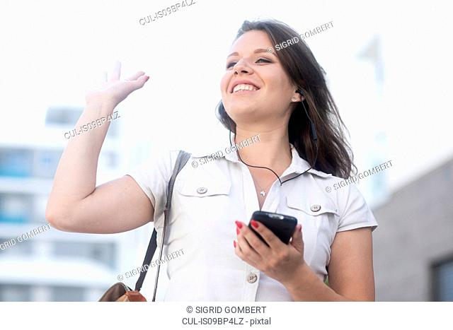 Woman holding smartphone and waving