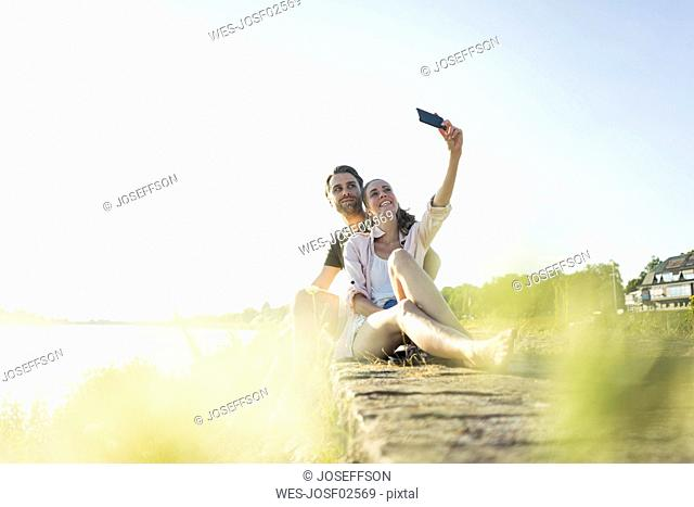 Happy couple at the riverside in summer taking a selfie