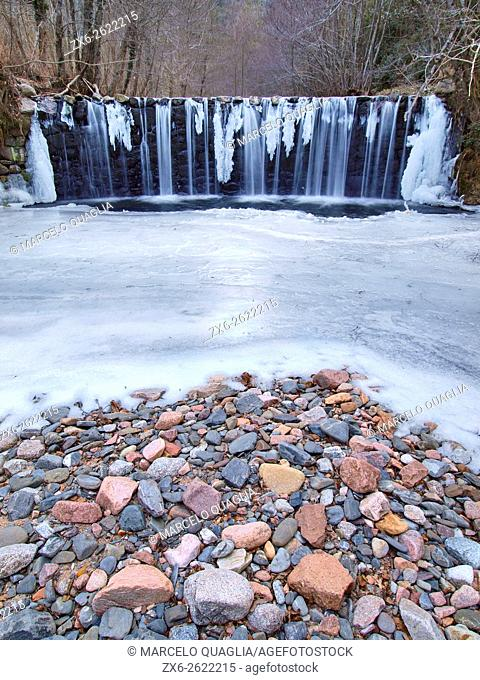 One of the several waterfalls at Riera Major stream frozen and with stalactites. Viladrau countryside in wintertime. Montseny Natural Park