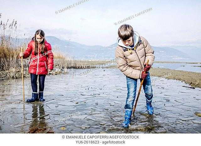 Children playing in the water of Lake Maggiore in the winter, Italy