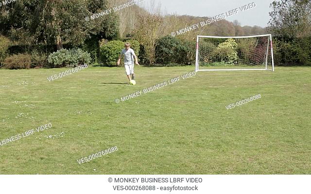 Young boy scores goal whilst playing football in garden.Shot on Sony FS700 in PAL format at a frame rate of 25fps