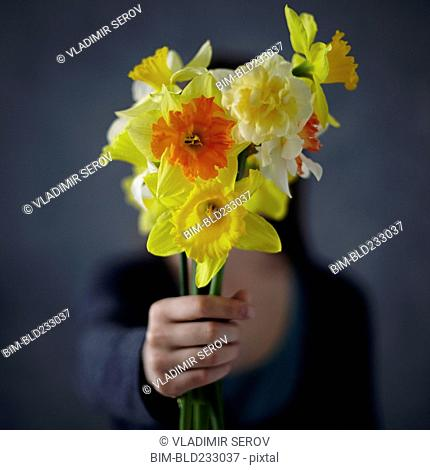 Caucasian girl showing bouquet of flowers
