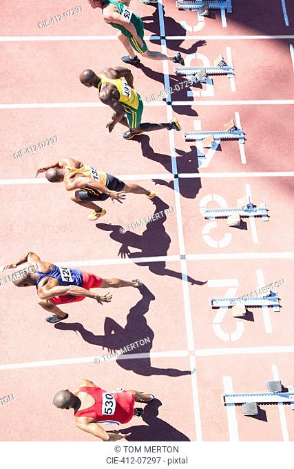 Sprinters taking off from starting blocks on track