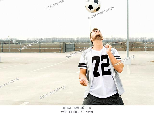 Young man heading soccer ball on parking level