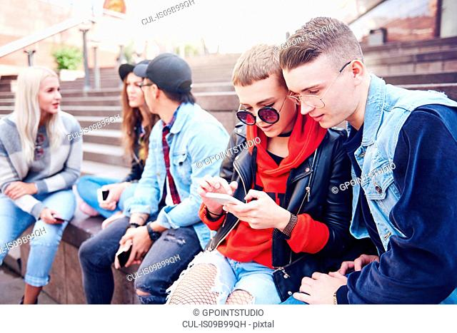 Five young adult friends looking at smartphone and talking on city stairs