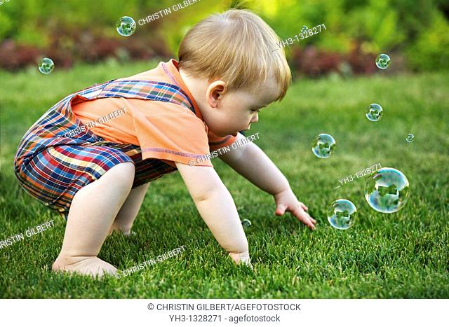 Portrait of a toddler playing with bubbles in the garden
