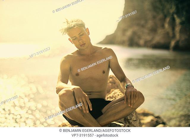 man sitting on rock at beach. At Agriomandra, Crete, Greece