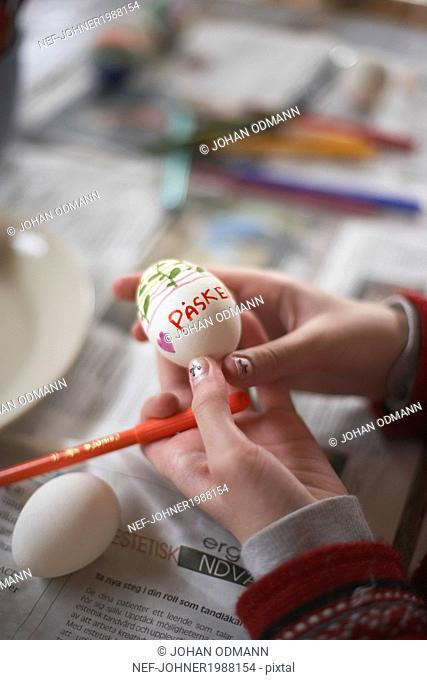 Girl painting Easter egg, close-up