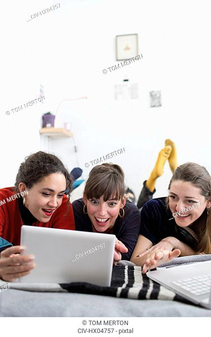 Young women friends hanging out, using digital tablet on bed