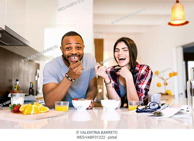 Young couple having breakfast in the kitchen