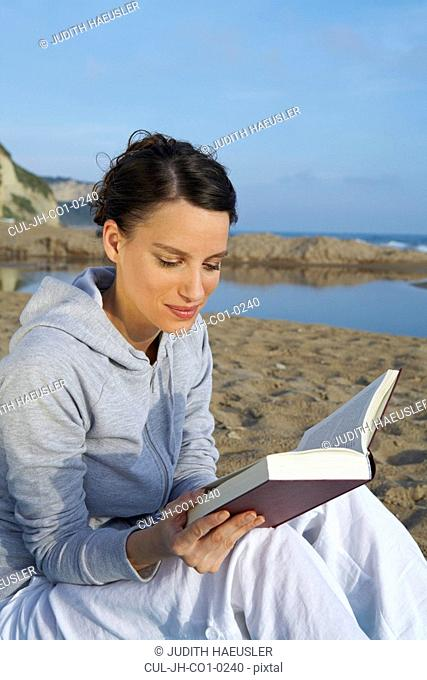 Young woman on beach portrait reading a book sea and sky in background