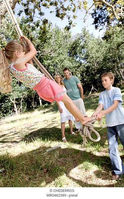 Boy pulling his sister on a rope swing with their parents in the background